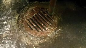 Water running down a rusty old drain in a gully stock footage