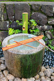 Water running out through bamboo pipe to stone water basin, Japa Stock Photography