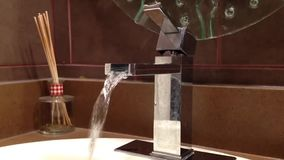 Water running out of a silver faucet stock video footage
