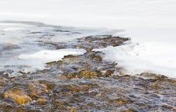 Water running over golden rocks in spring. Stock Image