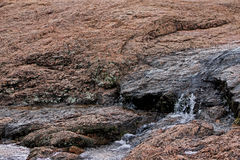 Water running over rocks and eroding over time Royalty Free Stock Image