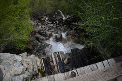 Water running under a small wooden foot bridge stock photo