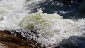 Water rushes over a rock ledge in a river. stock video