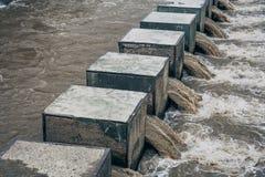 Water rushing through dam stock photography