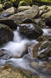 Water Rushing down Rocks. Long exposure of water from a stream pouring over rocks Stock Image