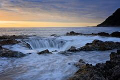 Water rushing into Thor`s Well during dramatic sunset Cape Perpetua Oregon