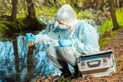Water sampling by an experienced ecologist. From a forest river stock photo