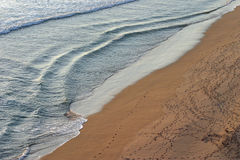 Water and sand. Ocean water with footprints on the sand Stock Photo