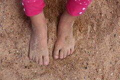 Water on Sand. Close up view of a toddlers feet covered in sand Royalty Free Stock Image
