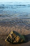 Water near the beach with a single rock Royalty Free Stock Photos