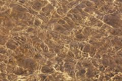 Water, sandy bottom. Clear sea water and sandy bottom background. Sand through the transparent water texture stock image