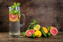 Water Sassy with lemon, grapefruit, orange, mint, cucumber and g. Inger, selective focus, on wooden background Royalty Free Stock Image