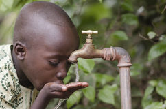 Water scarsity in the world symbol. African boy begging for wate. Water scarcity in the world symbol. African boy begging for water. In places like sub-Saharan Royalty Free Stock Photography