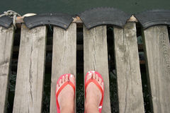Water scary. Woman feet on the dock Stock Photography