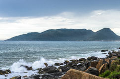 Water sea waves splashing on sea rocks on sea shore and a mountain. On the background. Long exposure photo at Morro das Pedras, Florianopolis, Brazil stock images