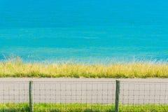 Water Seelandschaft mit Zaun und Straße Lizenzfreie Stockfotos