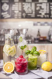 Water served in carafe and sorbets. Cherry, mint and lemon sorbet served in elegant cups. shown with carafe filled water with lemon and lime everything against Stock Image