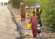 Water Shortage. Girls travel miles barefooted to bring water for their home royalty free stock photo