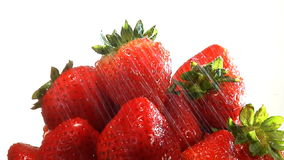 Water showers on bowl of organic strawberries stock video footage