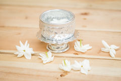 Water in silver bowl with Jasmine flower. Jasmine flower on silver tray, Thai white flower on wood background Royalty Free Stock Photos