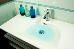 Water in Sink. Blue modern bathroom in a house Stock Photos