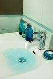 Water in Sink. Blue modern bathroom in a house Stock Photo