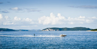 Water skier in the bay. Cutter and sportsman making water-skiing in the sea bay against horizon, mountains and deep blue sky Royalty Free Stock Photos