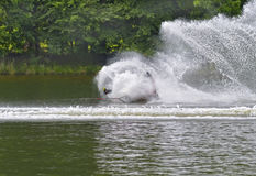 Water Skier Falling. A teenage boy water skiing during a tournament, falling on the course in a unique circular splash stock image