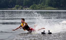 Water Skier falling and about to crash into a lake. Dramatic picture of a young male water skier just as he is about to hit face-first into the water Stock Photos