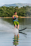 Water-Skiing Slalom Fun. Mature male water-skiing slalom single ski on glass mirror waters Royalty Free Stock Images