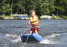 Water skiing. A little boy water skiing on a zip sled Royalty Free Stock Photo