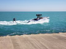 Water skiing. After a speed boat in a blue water near a shore Stock Photos