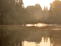 Water Skiing at Sunrise. Early-morning water skier on the water just as the sun rises over the lake Stock Image