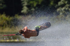 Water Skiing Tricks Athlete Roll. South African Champs Water Skiing in the tricks short ski category of the male skier athlete in a mid air roll hanging onto the Stock Image
