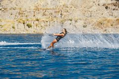 Water skis glides on the waves, female athlete on Aegean Sea, Greece Royalty Free Stock Images