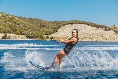 Water skis glides on the waves, female athlete on Aegean Sea, Greece Royalty Free Stock Photo