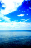 Water And Sky. Blue water and sky with white clouds. Saturated blue coloration royalty free stock photo