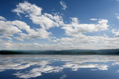 Water and sky. Fluffy clouds in the bright blue sky. Sky reflection on the water surface Royalty Free Stock Photography