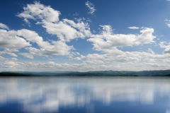 Water and sky. Fluffy clouds in the bright blue sky. Sky reflection on the water surface Stock Images
