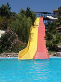 Water slide. Red and yellow water slides surounded by trees and flowers ending in clear blue swimming pool Stock Photography