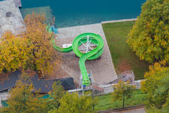 Water slide. Children's green color water slide near the lake in autumn, view from above royalty free stock photos