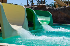Water slides at aqua park. Close up, ending in the pool Stock Photos