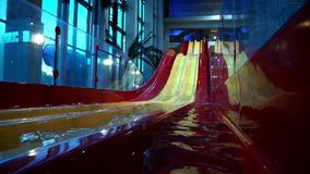 Water slides and pool in aqua park. Multicolored water slides in summer amusement park. Attractions in aqua park. Water slides and pool in aqua park stock video