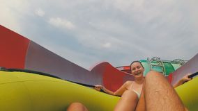 Water slides pov. Guy with girl on the inflatable circle descends from the water slides. Thailand. Water slides pov. The guy with the girl on the inflatable stock video footage