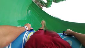 Water slides pov. Man on inflatable ring goes down with water slides. Slow Motion. Water slides pov. Man on inflatable ring goes down with water slides. First stock video footage