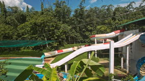 Water Slides in Tropical Water-park Complex. Different water slides in tropical waterpark complex among green plants in Vietnamese resort city stock video
