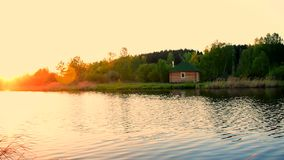 Water of the small lake slowly moving in sunset with small house on the shore stock footage
