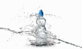 Water. Small plastic water bottle with water drops and splash on Stock Photo