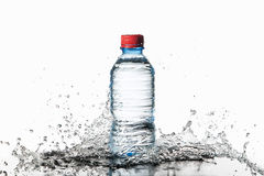 Water. Small plastic water bottle with water drops and splash on Stock Images