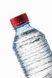 Water. Small plastic water bottle with water drops on white back Royalty Free Stock Photography